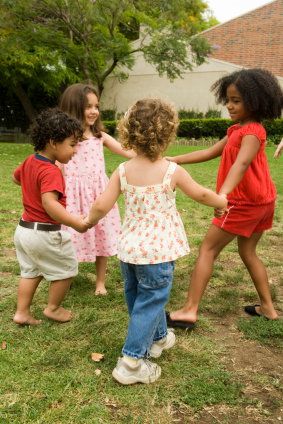 Four children holding hands in a circle and playing together