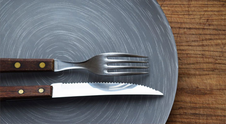 Knife and fork resting on a grey plate