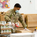 National Guard volunteer helping pack food at Norwthwest Harvest