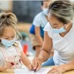 Early Childcare worker wearing mask, teaching child in mask