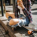 Youth on skateboard sitting on urban street