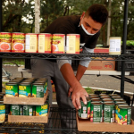 worker stacking cans of food